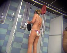 Voyeur beauty with a smooth body in the women's shower room.